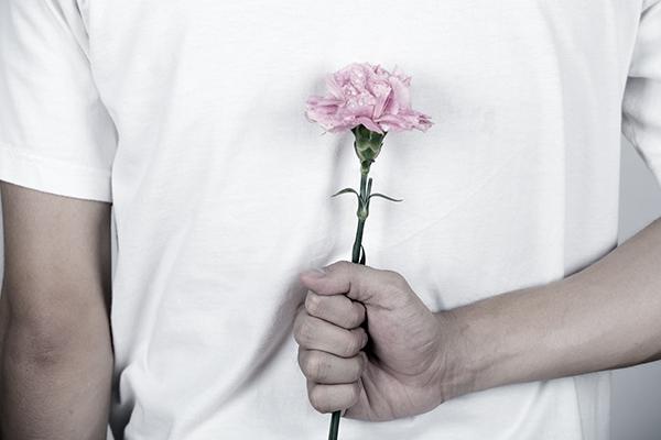 pink carnation hiding behind of man