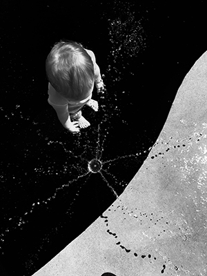 Matthew Shaffer artwork entitled Maisie - overhead picture of a child dropping a rock into a dark abyss