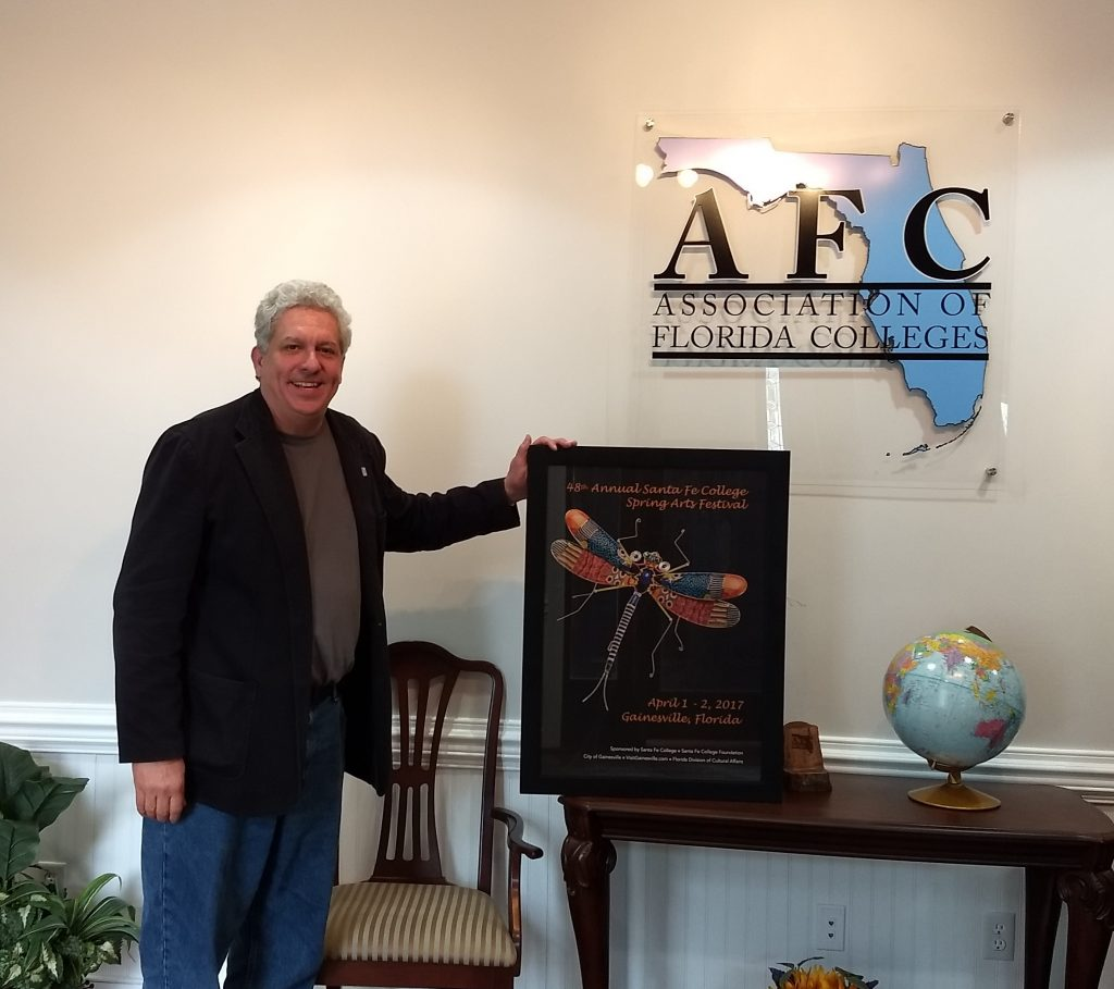 Santa Fe College AFC Chapter President Tom Mason poses with the SF Spring Arts poster at the new AFC headquarters in Tallahassee