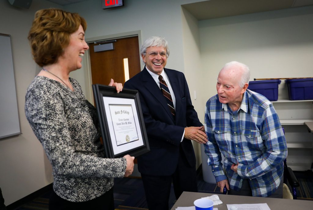Col. Arley W. McRae, USAF Retired, right, is presented a plaque by Lisa M. Prevatt, Chair, and President Dr. Jackson Sasser after being  named the first Trustee Emeritus at Santa Fe College during the Board of Trustees meeting.