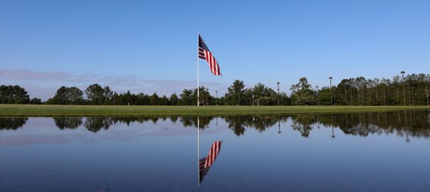 The flag is reflected in a puddle of water after a few days of heavy rain