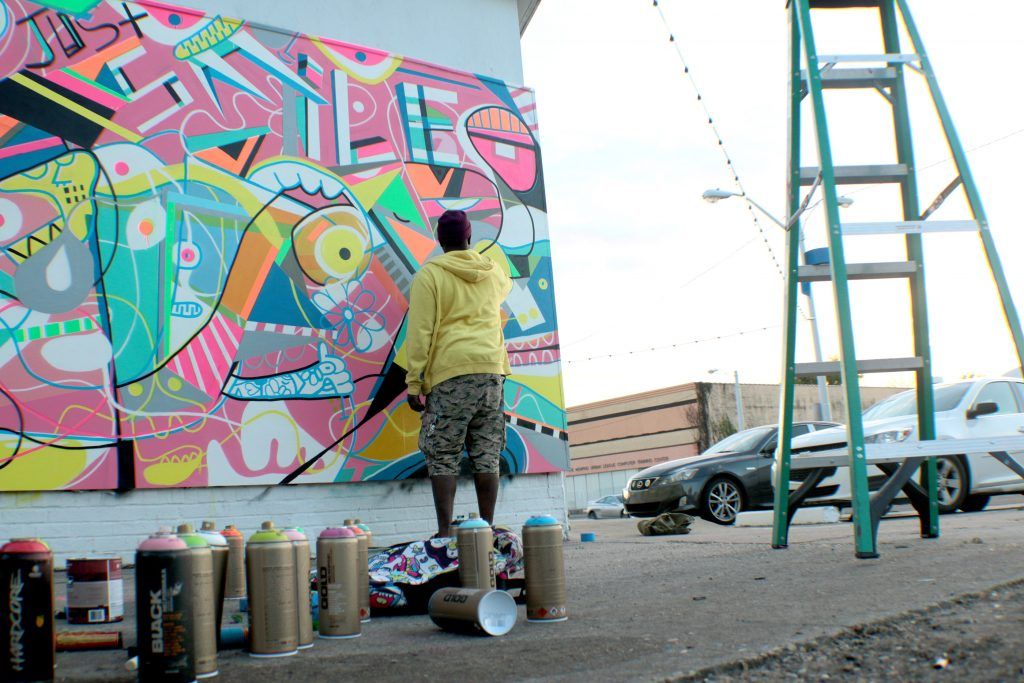 Artist Kevin Bongang working on one of his murals