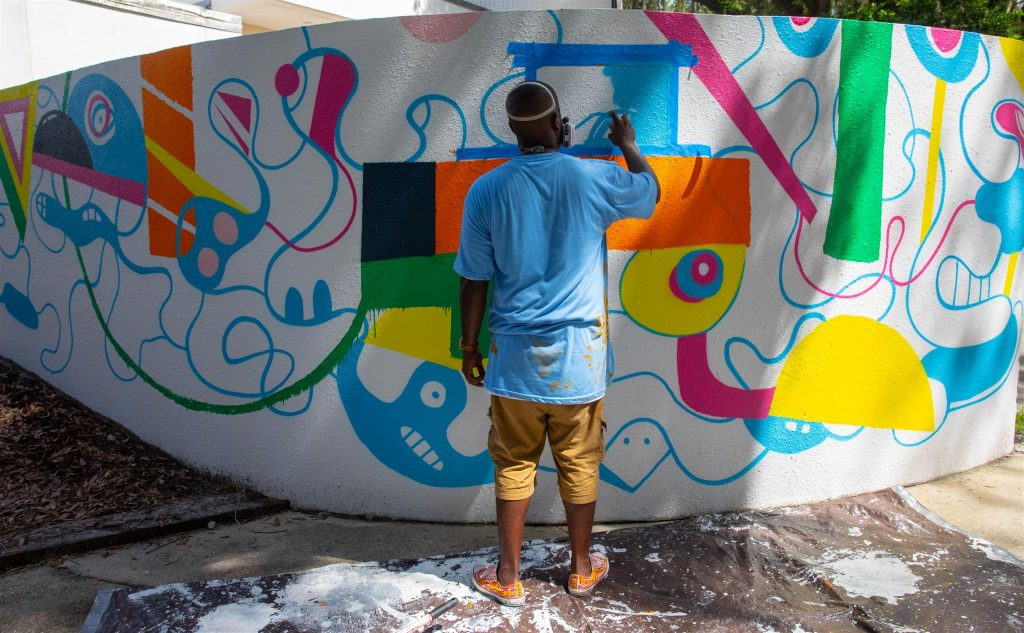 Kevin Bongang working on a mural on Santa Fe College's Northwest Campus.