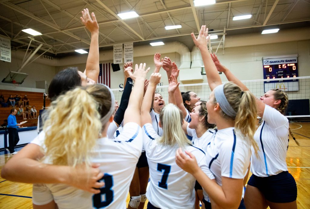 Saints volleyball players celebrating winning the Panhandle Conference