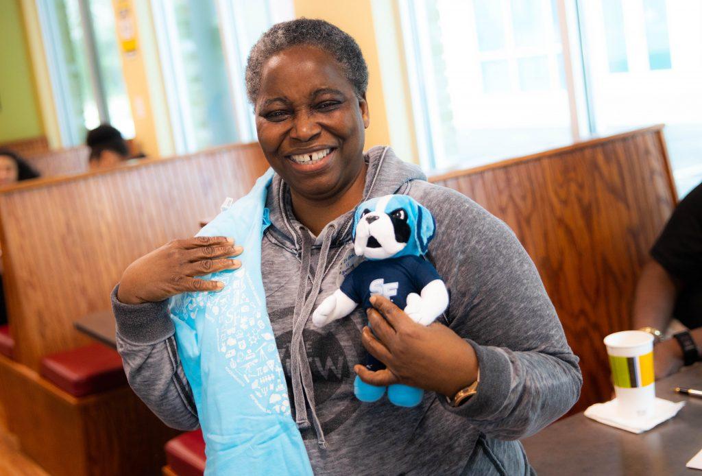 Bea Awoniyi holding a plush Caesar Saint mascot and a Santa Fe College T-shirt