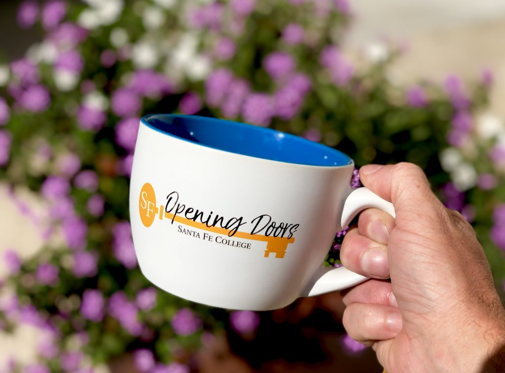 Santa Fe College Opening Doors mug photographed in front of some azaleas