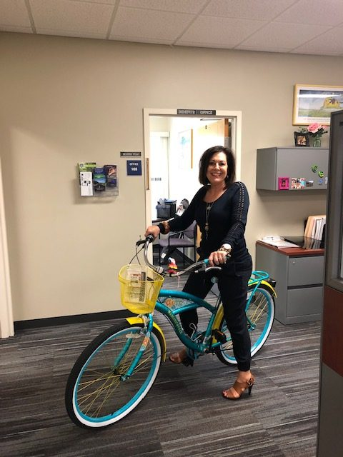 Beverly Polk sitting on a beach cruiser bicycle in the HR office.