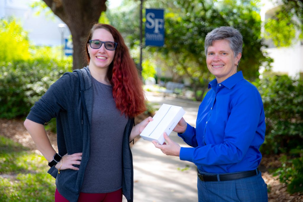 Cheryl Calhoun, PhD, Dean of Access and Inclusion, presents Megan Bossert with an iPad Mini on April 8, 2019 in Gainesville, Fla. Bossert won the iPad for completing the National Assessment of Collegiate Campus Climate (NACCC) survey.