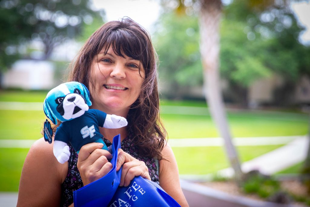 Sarah Cervone, SF Brand Ambassador for April 2019, holding a plush Caesar mascot.