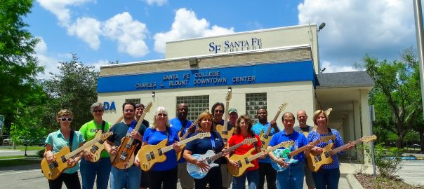 SF faculty members standing outside the Blount Center with guitars they made as part of the Guitars, Rockets and Robots program at the college.