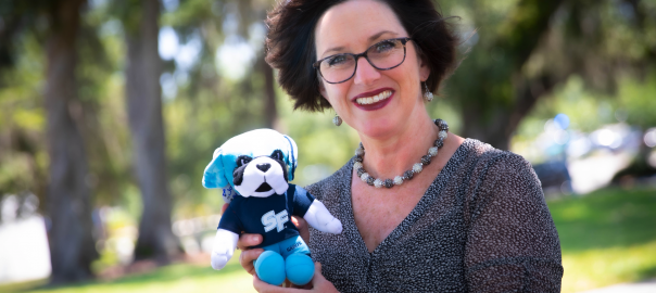 The May 2019 Santa Fe College Brand Ambassador Jodi Long with a plush Caesar doll.