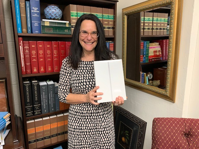 Patti Locascio standing in her office holding the iPad. A bookshelf full of law books is behind her.