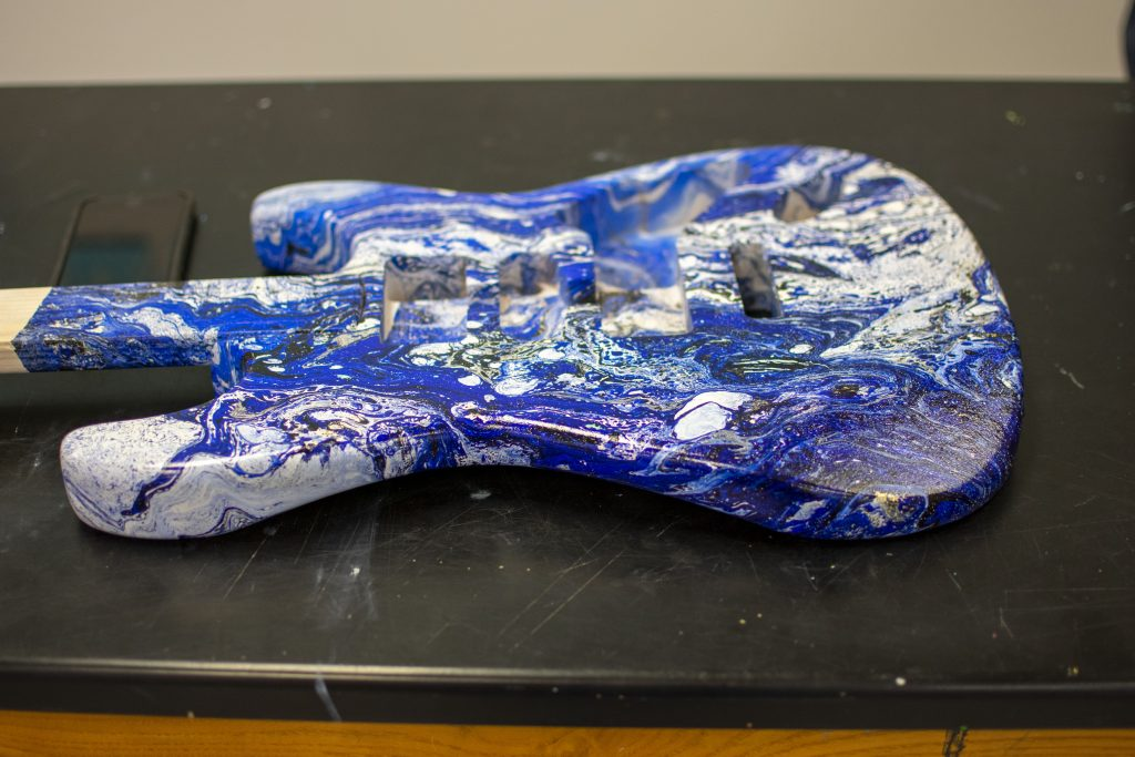 Guitar painted with blue swirl design.