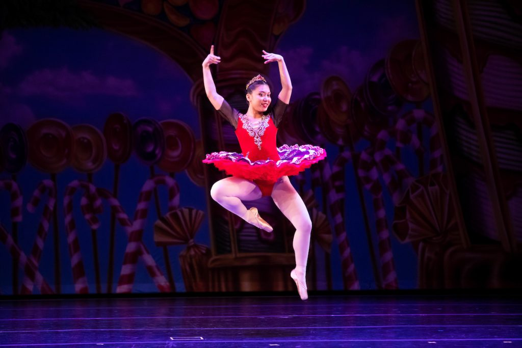 Ballerina dancing and jumping in the air during a performance.