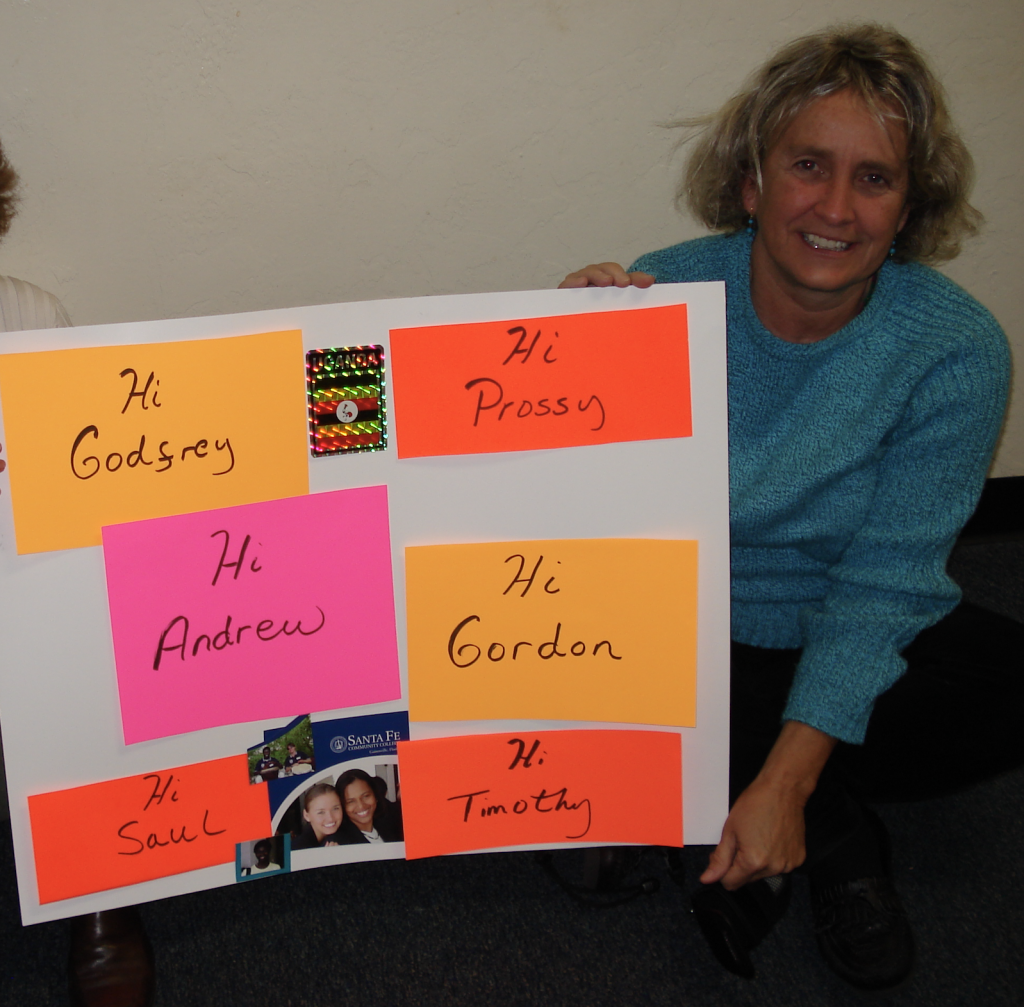 Carol Thomas in Africa holding a poster board sign with names of friends